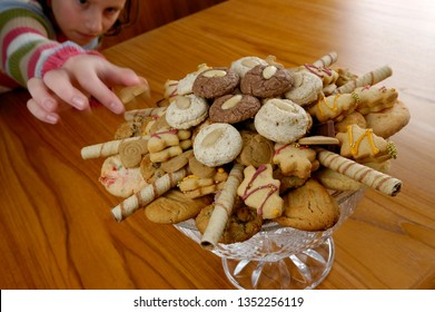 Girl taking a christmas cookie from the plate