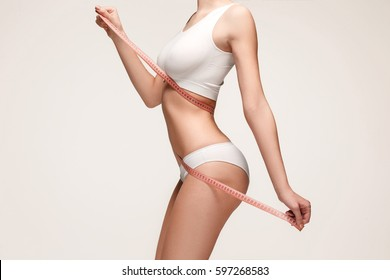 The girl taking measurements of her body, white background.
