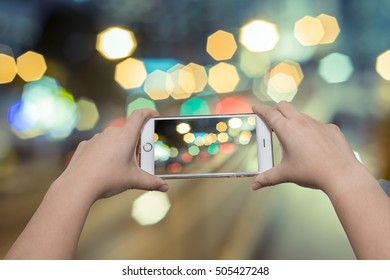 Girl taking night view photos using mobile phone on the street
