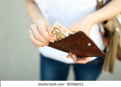 Girl is taking out a banknote of fifty euros from brown leather wallet on the street. Hands, money and wallet close-up.