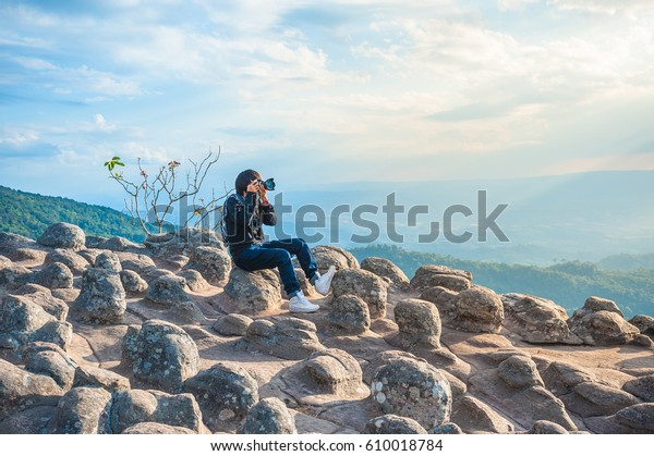 Girl taking photo of beautiful mountains with her DSLR camera on summer vacation hiking trip. Blue sky with clouds in the background.  Phu Hin Rong Kla National Park, Phitsanulok, Thailand