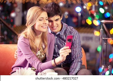 Girl taking photo with her boyfriend with mobile phone
