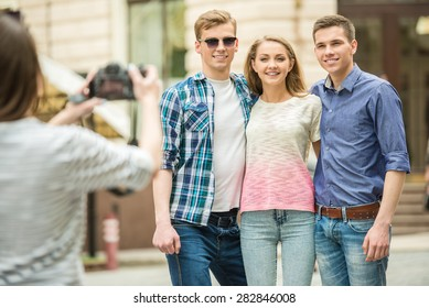 Girl taking photo of her friends. Double couple date outdoors.