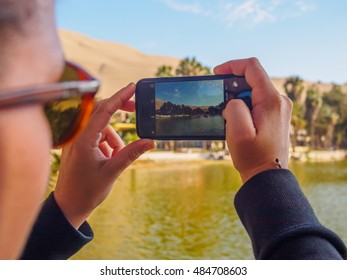 Girl taking photo of Huacachina oasis with smartphone
