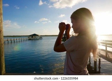 Girl taking a photo of a river landscape at sunset