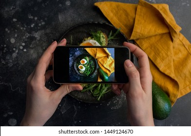 Girl taking photo of sandwich with eggs with smart phone at dark background. instagram photography blogging workshop concept.