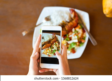 Girl taking photo of seafood in a restaurant first person view