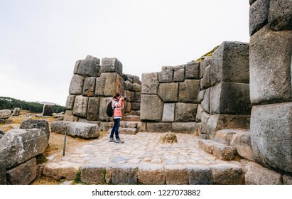 Girl taking photo of stone ancient wall in Sacsayhuaman