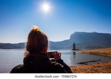 Girl taking photo at swamp in Sau reservoir, Catalonia, Spain.