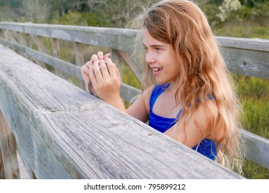 Girl taking a photograph from a nature boardwalk