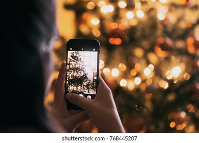 girl taking picture of christmas tree with her smartphone