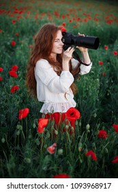 Girl taking picture on a professional camera in a poppy field