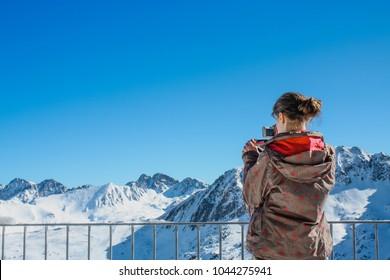 Girl taking picture of snowy mountain peaks in ski resort.