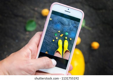 A girl is taking pictures of her legs in yellow boots on the phone. A summer rain concept.