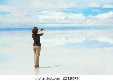 Girl taking pictures on a mobile phone in the middle of the lake Salar de Uyuni, Bolivia