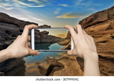 Girl taking pictures on mobile smart phone in Mountain stone cave 3000 boke in sunrise