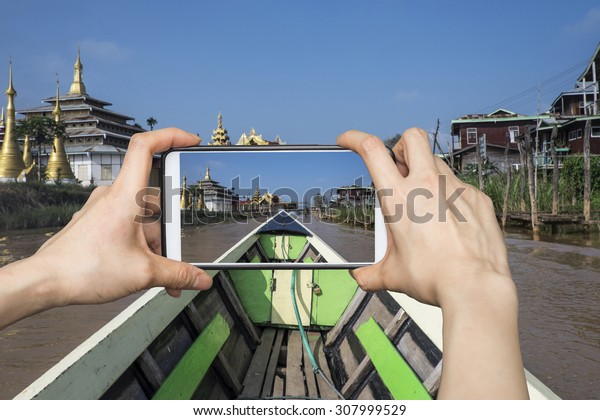 Girl taking pictures on mobile smart phone in boat at inle lake,Myanmar