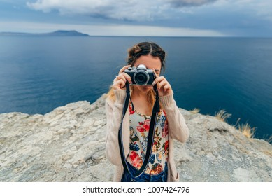 girl taking pictures outdoors on a retro camera on a summer vacation