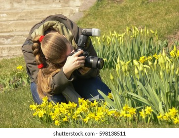 Girl taking pictures of spring flowers