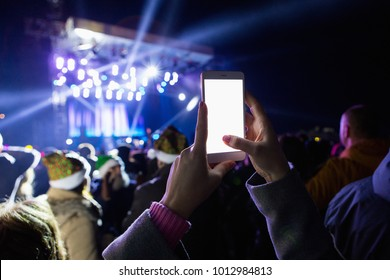 A girl is taking pictures of a street concert on the phone. Blank screen