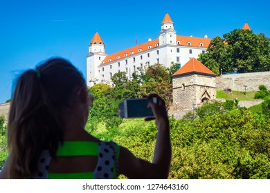 A girl is taking pictures of a white castle in Bratislava. Castle Bratislava. White Castle in Bratislava.Medieval castle on the hill against the sky, Bratislava, Slovakia.