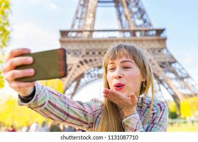 Girl taking a selfie and blowing a kiss in Paris with Eiffel Tower on background. Happy blonde young woman on a video call with her smartphone. Travel, technology and lifestyle concepts
