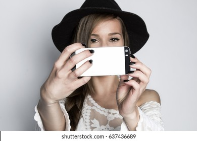 Girl taking selfie with phone, studio shot