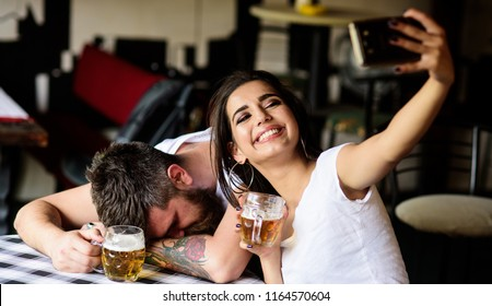 Girl taking selfie photo drunk boyfriend. Take selfie to remember great event. He appears too weak for her. Woman making fun of drunk friend. Man drunk fall asleep table and girl with full beer glass.
