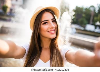 Girl taking selfie photo near fountain outdoors