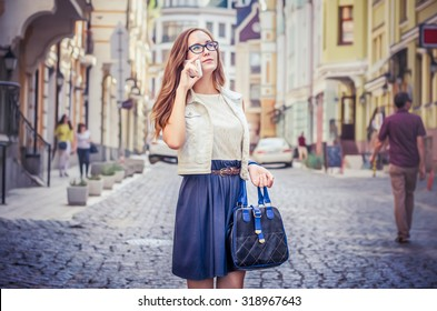 girl talking on the phone. Girl with a bag. against the backdrop of the city