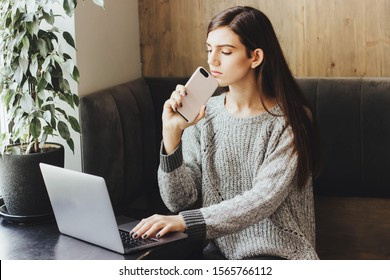 The girl is talking on the phone at the same time, working at the computer and typing a message in another smartphone in a stylish coffee shop. Productive young girl. Business lady working in a cafe.