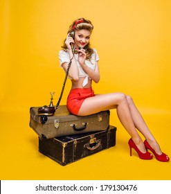 girl talking on the phone sitting on suitcases