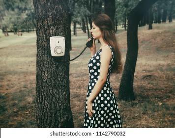 The girl is talking on the vintage disk phone hanging on a tree in the desert park. Photo with film camera effect