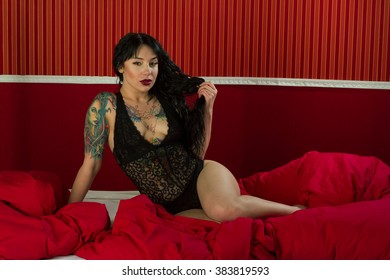 The girl with a tattoo in black lingerie posing on a bed.