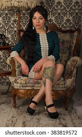 The girl with a tattoo in a green dress sitting in an old chair.