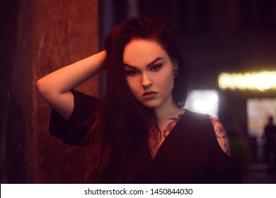 Girl in the tattoo, with piercing in the nose and tunnels in the ears. Beautiful girl, night portrait. The girl in neon lighting. Beautiful unconventional brunette. Girl with a professional make-u