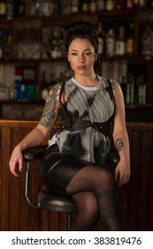 Girl with tattoos sitting on a chair near the bar.