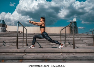 The girl with tattoos in sportswear does a warm-up before gymnastics. Doing yoga. Against the background of the stairs, in the summer in the city. Sports and healthy lifestyle.