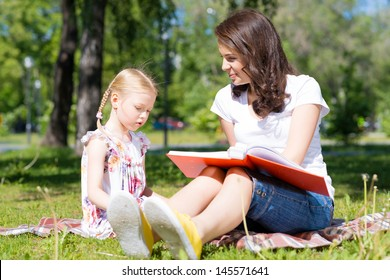 girl with the teacher reading a book together in the summer park