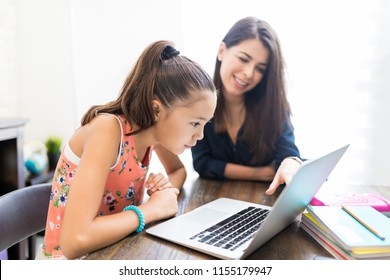 Girl and teacher using laptop during homeschooling at table