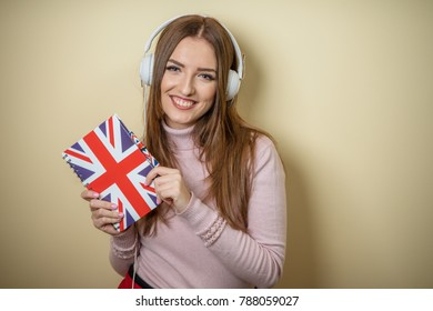 The girl teaches English with a notebook and headphones