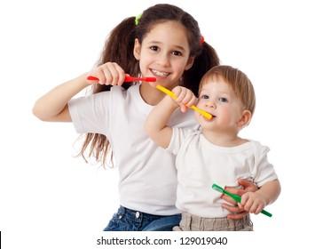 Girl teaches little boy brushing teeth, isolated on white