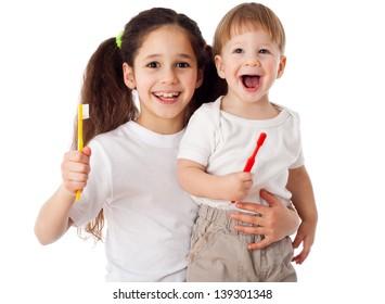 Girl teaches little boy brushing the teeth, isolated on white