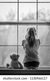 Girl and teddy bear looking out window