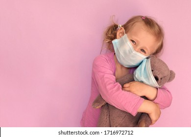 Girl with teddybear in face mask. Caucasian child wears facemask for protect during coronavirus Covid-19 epidemic.