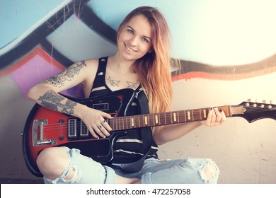 Girl teen sitting near a graffiti wall and plays electric guitar.