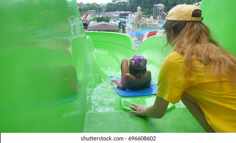 The girl teen in the water park. girl teen rolls downhill in the water park amusement park