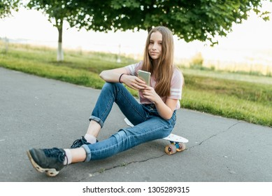 Girl teenager 10-12 years old, sits on board in hands of phone. In summer in city in casual jeans and a pink T-shirt. Communication in the Internet, in hands of holding a smartphone. Smiles and poses.