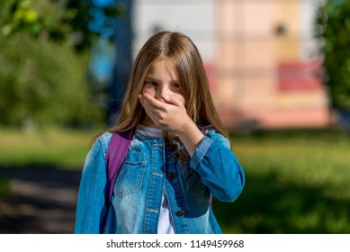 Girl teenager after school. In the summer in the park in nature. The hand closes his mouth. The concept of nausea, vomiting, do not say. Emotions are silent, quiet, without sound.