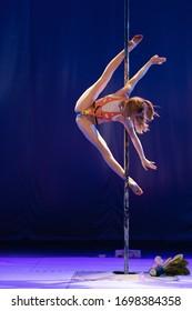 Girl teenager athlete gymnast shows an acrobatic performance on a pylon.